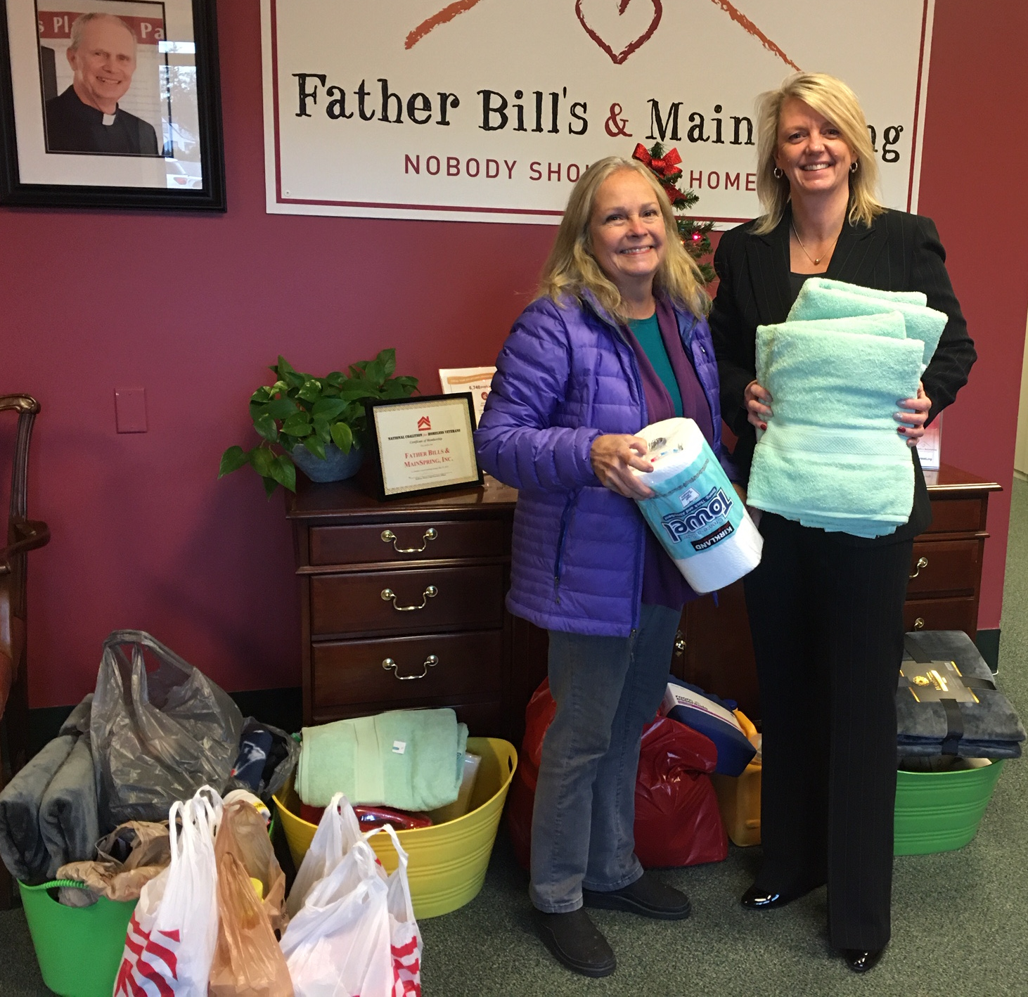 a picture of a woman holding some paper towels, surrounded by donations with a woman from Father Bills